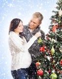 Un couple décorant l'arbre de Noël (femme enceinte) Photo libre de droits