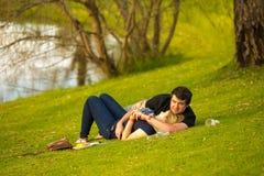 Un couple détendant sur l'herbe à l'événement de vin Photographie stock libre de droits