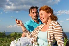 Un couple détendant sur l'herbe verte et le ciel bleu Couplez le mensonge sur l'herbe extérieure avec le fond de l'eau et de ciel Photos stock