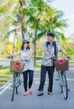 Un couple d'ami est marchant et causant avec le bicy Images stock