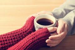 Un couple dans des mains de chauffage d'amour avec une tasse chaude de thé Photographie stock libre de droits