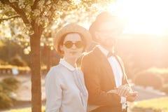 Un couple dans l'amour au coucher du soleil dans des chapeaux se tient avec leurs dos en Th Photographie stock