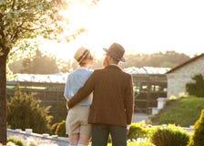 Un couple dans l'amour au coucher du soleil dans des chapeaux se tient avec leurs dos en Th Photos libres de droits