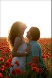Un couple dans l'amour dans un pavot met en place au coucher du soleil Photos stock