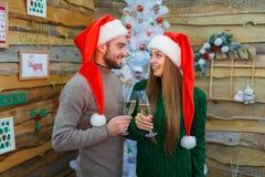 Un couple dans l'amour dans des chapeaux rouges de Noël boit le champagne et le regard mignon à l'un l'autre indoors Images libres de droits