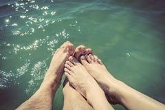 Un couple dans l'amour mouillant leurs pieds en mer Vacances d'été cru Images libres de droits