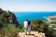 Un couple dans l'amour regarde la mer de la falaise Photographie stock libre de droits