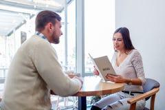 Un couple dans l'amour se reposant dans un café et regardant le menu Photographie stock