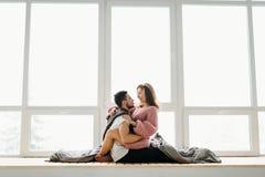 Un couple dans l'amour se repose sur le rebord de fenêtre Nouveaux mariés ayant l'amusement Photographie stock