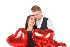 Un couple dans l'amour tenant des boules d'hélium sous forme de coeur D'isolement Photographie stock
