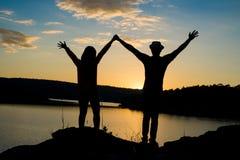 Un couple dans l'amour tenant des mains observant le beau coucher du soleil lumineux Photographie stock
