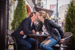 Un couple dans l'amour : un type et une fille embrassent à une table dans un café Photos stock