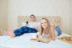 Un couple dans le lit prend le petit déjeuner, TV de observation, lisant un livre images stock