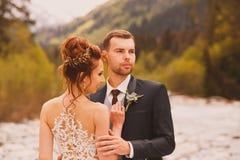 Un couple dans une robe de mariage avec un bouquet des fleurs et des verts est dans les mains sur le fond des montagnes à Photo libre de droits
