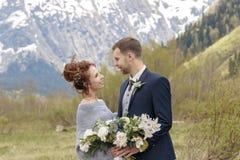 Un couple dans une robe de mariage avec un bouquet des fleurs et des verts est dans les mains sur le fond des montagnes à Photographie stock