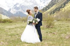 Un couple dans une robe de mariage avec un bouquet des fleurs et des verts est dans les mains sur le fond des montagnes à Photos stock