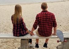 Un couple de la séance arrière sur un banc Images stock