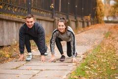 Un couple de sports est engagé dans un parc d'automne faisant un bas début pour le fonctionnement images stock