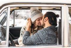 Un couple de Valentine se reposant à l'intérieur d'une rétro voiture de neige et embrassant dans une fille romantique de beauté d Image libre de droits