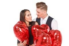 Un couple doux regarde l'un l'autre et l'embrasse parmi les boules D'isolement sur le fond blanc Images libres de droits