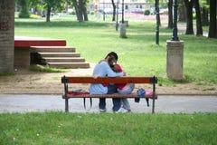 Un couple embrassant sur un banc image stock