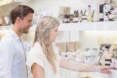 Un couple examinant un échantillon de produits de beauté Photo stock