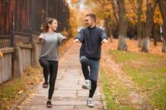 Un couple fait des sports en parc en automne Soulevez vos genoux aux niveaux de votre coffre dehors Image libre de droits