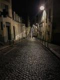 Un couple flâne dans la distance en bas d'une rue pavée en cailloutis de Paris la nuit Photos stock