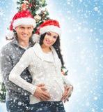 Un couple heureux attendant le bébé à Noël Image libre de droits
