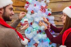 Un couple heureux décore un arbre de Noël le réveillon de Noël indoors Images libres de droits