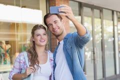 Un couple heureux de sourire prenant des selfies Photographie stock