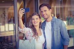 Un couple heureux de sourire prenant des selfies Image stock
