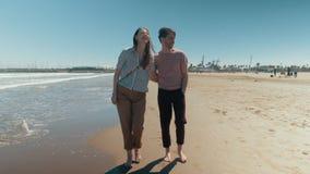 Un couple heureux descendant la plage tenant nu-pieds des mains banque de vidéos