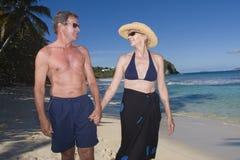 Un couple heureux marchant sur la plage Photo libre de droits