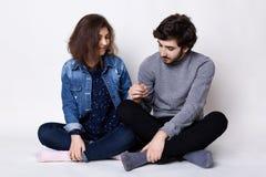 Un couple heureux se reposant sur le plancher a croisé des jambes se tenant des mains du ` s étant heureuses et heureuses d'être  Image stock