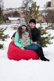 Un couple, un homme et la femme se reposent dans un fauteuil rouge dans la perspective d'un couvert de neige, parc d'hiver Photographie stock