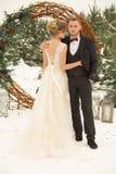un couple un homme et une femme se tient dans la perspective d'une forêt d'hiver, un cercle des fleurs décorées des vignes, a photo stock