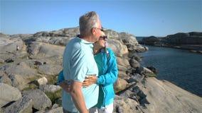 Un couple mûr affectueux heureux apprécie une promenade parmi les pierres côtières sur le bord de la mer banque de vidéos