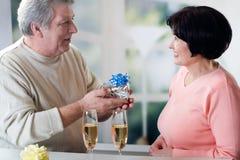 Un couple mûr heureux célébrant leurs années ainsi que le rouge Image stock