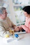 Un couple mûr heureux célébrant leurs années ainsi que le rouge Photos stock