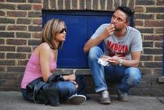 Un couple mangeant des casse-croûte sur la rue Photos libres de droits