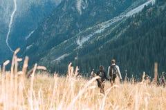 Un couple marchant dans un pré devant un paysage montagneux Photos libres de droits