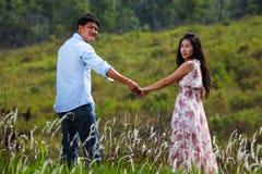 Un couple marchant par une prairie Image libre de droits