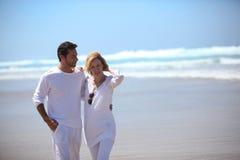 Un couple marchant sur une plage Photo libre de droits