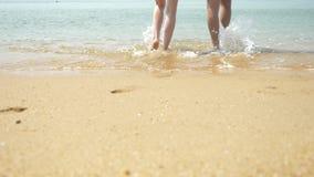 Un couple marche le long de la plage un jour ensoleill? clair Ils tiennent des mains et le baiser les pieds de marche des hommes  clips vidéos
