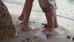 Un couple marche le long de la plage un jour ensoleill? clair Ils tiennent des mains et le baiser Les pieds des hommes et de femm banque de vidéos