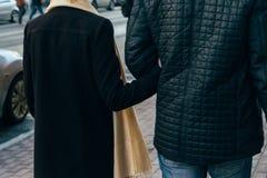 Un couple marche, marche par la ville, tenant des mains, bras, vue arrière Photos stock