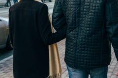 Un couple marche, marche par la ville, tenant des mains, bras, vue arrière Photographie stock