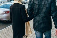Un couple marche, marche par la ville, tenant des mains, bras, vue arrière Photos libres de droits