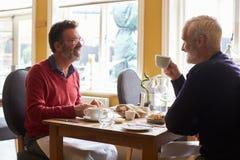 Un couple masculin gai prenant le déjeuner dans un restaurant, vue de côté Image libre de droits